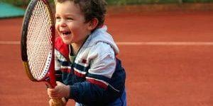 Toddler smiling playing tennis